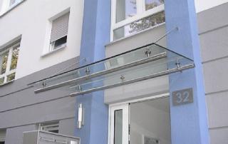 Punktgehaltenes Vordach Verglasung VSG aus 2x TVG über Edelstahlzugstäbe an Fassade abgehängt und über Befestigungskonsolen mit Fassade verschraubt.