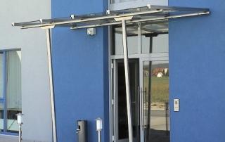 Liniengelagertes Glasvordach mit Stützen aus Edelstahl Rundrohr d=60 mm.