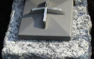 Weihwassergefäß aus Stein mit Stahldeckel und Kreuz.