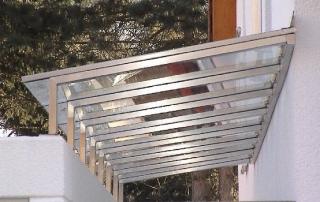 Überdachung aus Edelstahl-Winkel-Profilen punktuell an Fassade verschraubt und an Fertiggarage aufgeständert, Ausladung ca. 1000 mm, Auflage aus KU-Doppelstegplatten, inkl. Überhangstreifen an der Hausfassade.