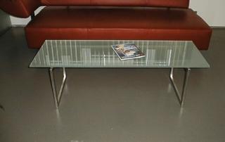 Wohnzimmertisch aus Edelstahl Vierkantrohr und aufgelegter Glasscheibe.