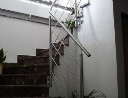 Treppengeländer bestehend aus Rundrohrpfosten d=42mm, inkl. waagrechten Stäben d=12mm und aufgesetztem Edelstahlhandlauf, über Flanschplatten im Treppenauge befestigt.