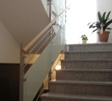 Treppengeländer aus Edelstahl Vierkantpfosten 40x40mm, inkl. zwei Stck. Obergurten d=12mm und einem Untergurt d=12mm, inkl. VSG Verglasung über Punkthalter befestigt, inkl. Holzhandlauf, über Flanschplatten im Treppenauge befestigt.
