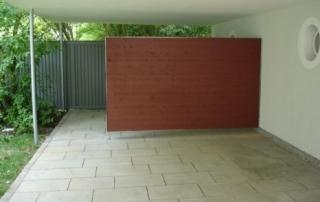 Müllplatzabtrennung aus Edelstahlrahmen mit Holzbeplankung, über Scharniere an der Wand befestigt.