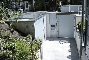 Mülleinhausung bestehend aus stabiler Edelstahlrahmenkonstruktion für VSG Verglasung, über Pressprofile befestigt, inkl. 2-flügeliger Tür mit einseitiger ALU-Verblendung nach RAL-Standard pulverbeschichtet, inkl. verstellbarer Edestahlscharniere und Anschlag.